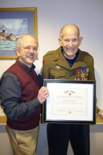 David Kroontje, left, presents his friend Dr. Lauren Brown with a certificate for a Bronze Star Medal, First Oak Leaf Cluster, for Brown's Army service in Europe in World War II.
